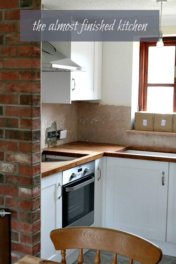Country cottage early Feb 2016 - the almost finished kitchen with white cupboards, wooden worktop and stainless steel appliances