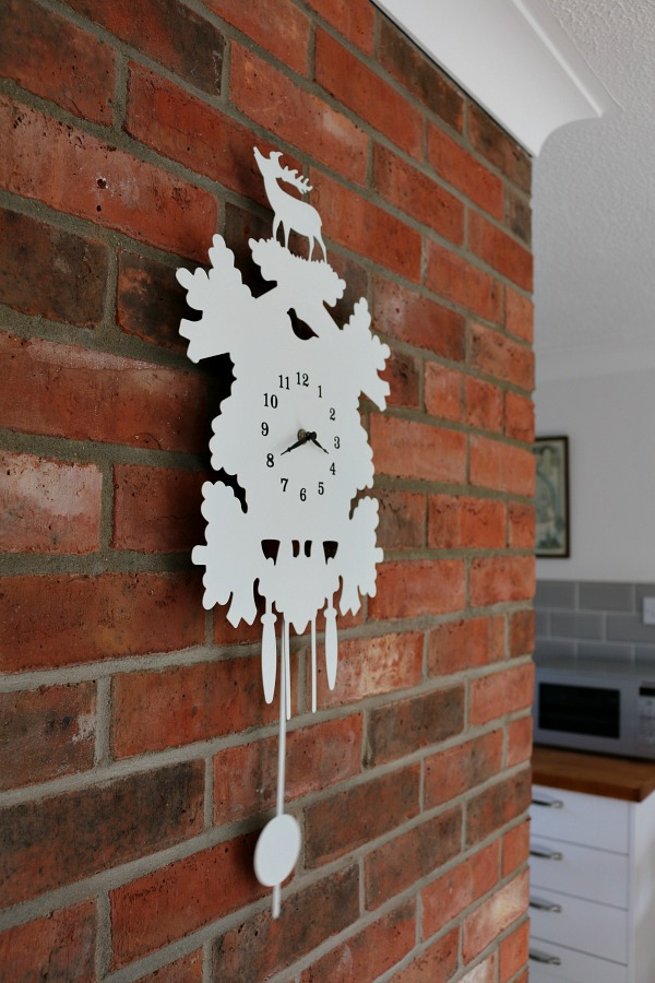 brick wall, white cuckoo clock