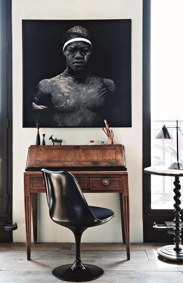 """Dans un quartier populaire de l'Est parisien, d'anciens bureaux dénués de charme ont fait place à un spacieux loft au décor chaleureux et singulier, sur fond de briques et de béton brut. Un pêle-mêle d'idées et d'influences avec vue plongeante sur le Sud de Paris. -- Photo de Denis Rouve, bureau de famille, chaise """"Tulip"""", Silvera, et guéridon Napoléon III."""