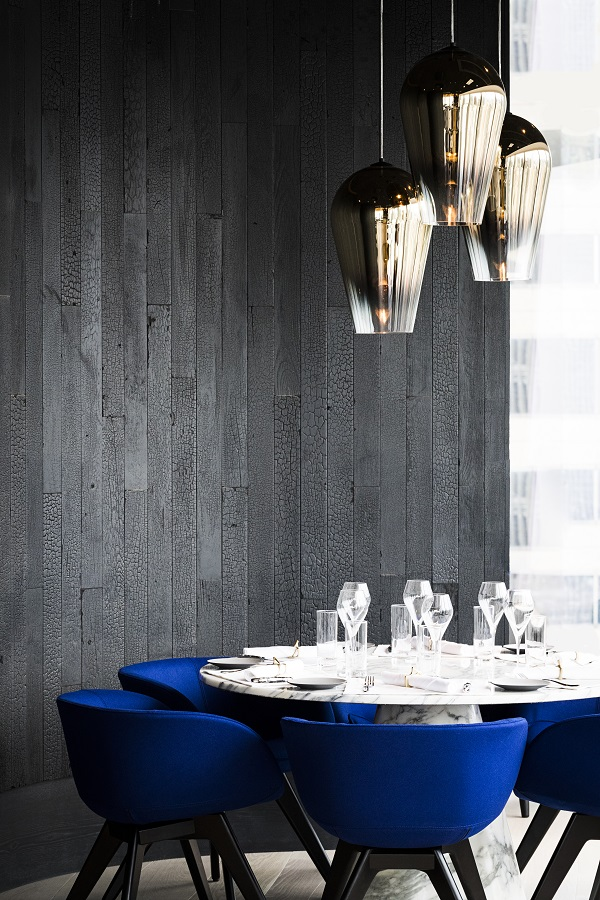 blackened wood walls, a cluster of metallic lights and plush blue seating