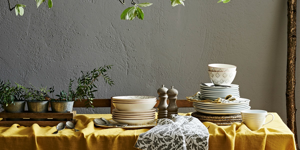 add a sunny tablecloth and lots of greenery to your autumn table settings