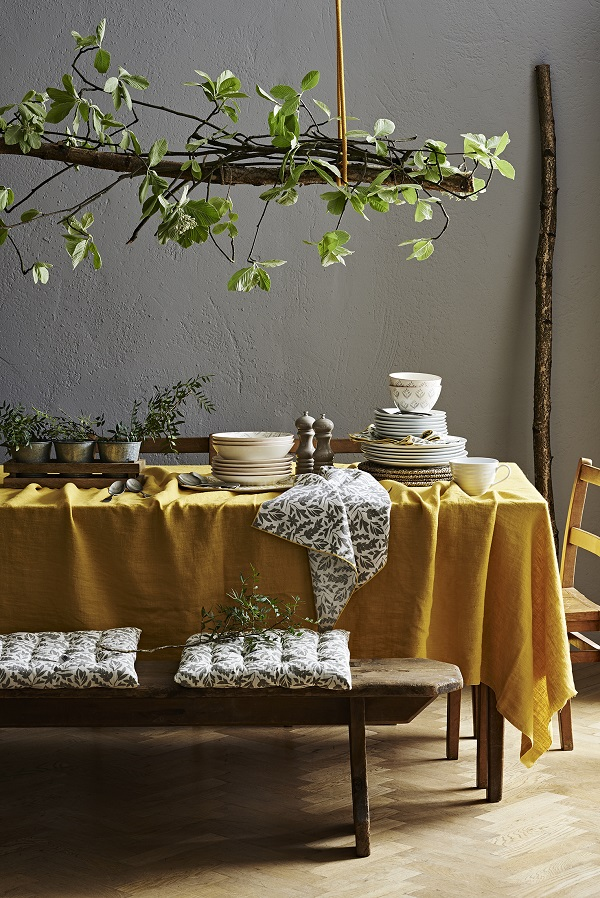 autumn dining and candlelit suppers are made cosier with a yellow tablecloth and some green plants
