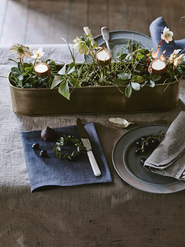 An autumnal table setting with a metal planter, plants and tealights