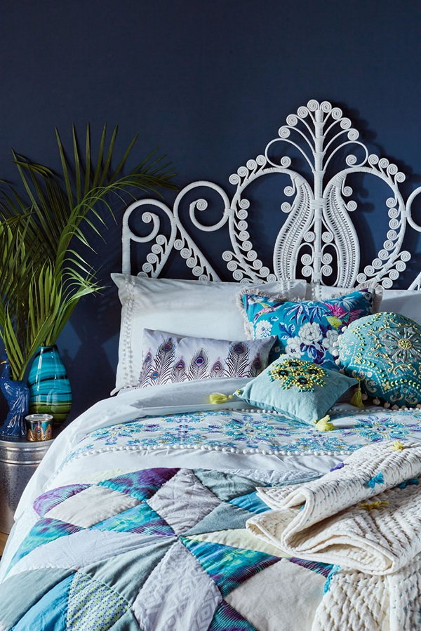 Bohemian Style = a rattan headboard, potted plants and layers of pattern