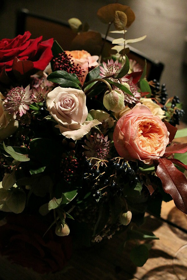 Vases of gorgeous roses and winter berries