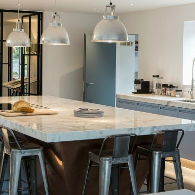 Blue kitchen cupboards with marble worktops and industrial details