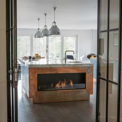 Blue kitchen cupboards with marble worktops and industrial details and a copper clad fire-box