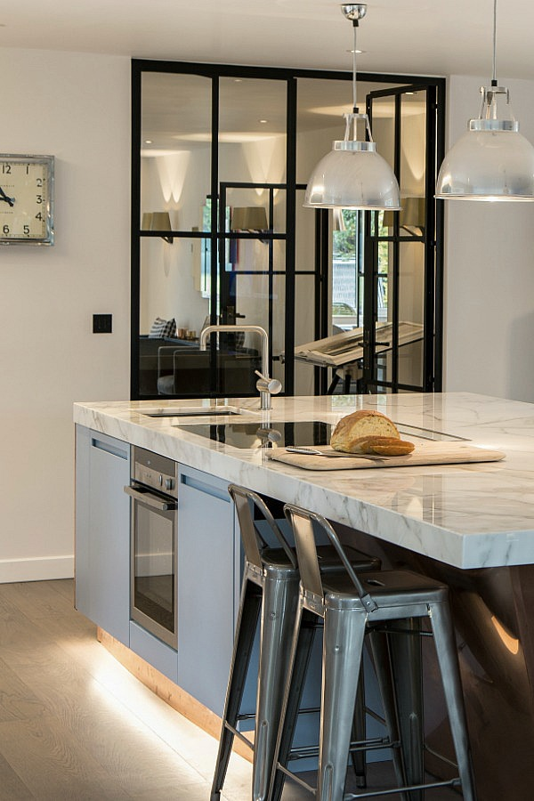 Blue kitchen cupboards with marble worktops and industrial details and internal Crittall windows