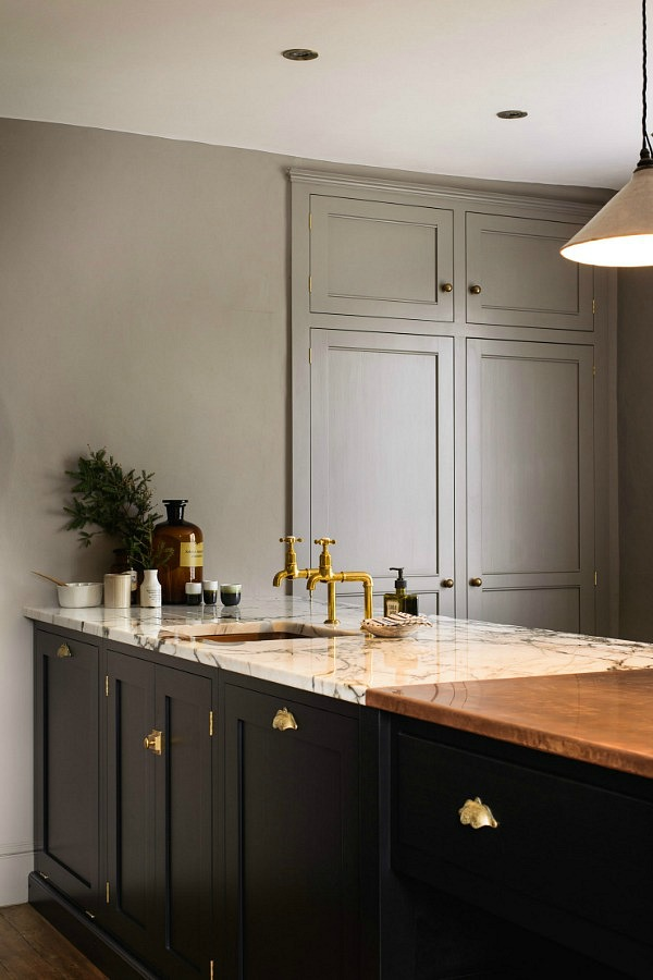 the artisan cup handles, wooden Bum stool and simple pendant lights all add to the simple country kitchen style.