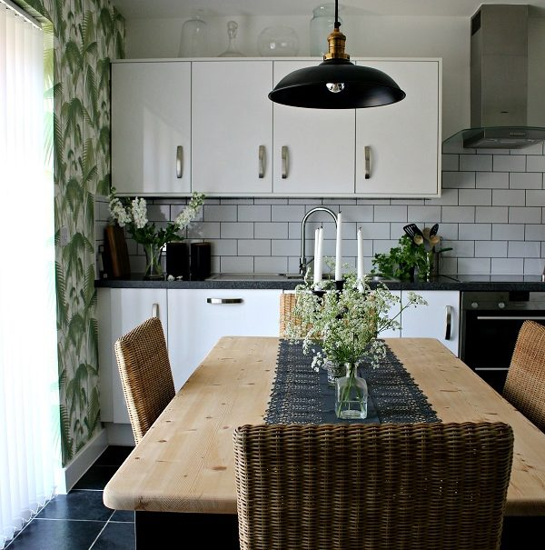 tropical palm wallpaper in a monochrome kitchen with wooden table