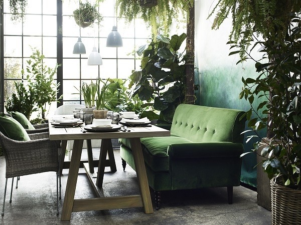 a Garden Room Filled with Plants and a velvet green sofa