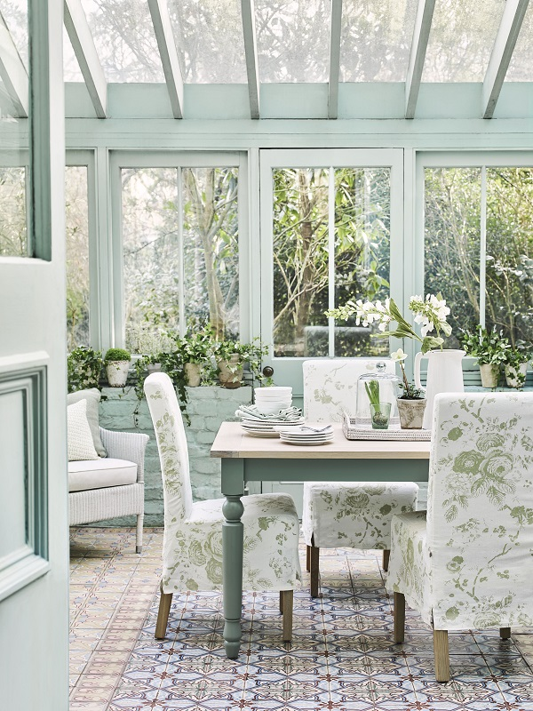 a Garden Room Filled with Plants and pastel prints