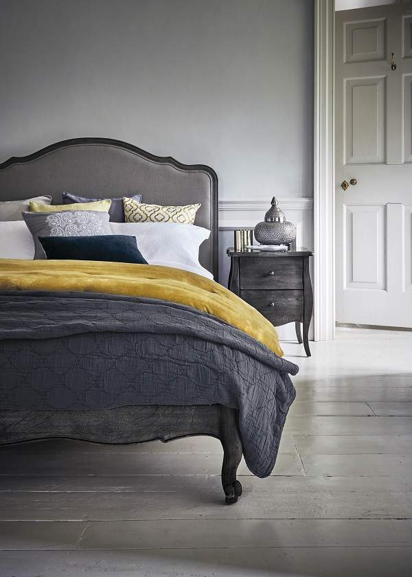 yellow in home decor with a velvet throw in a grey bedroom