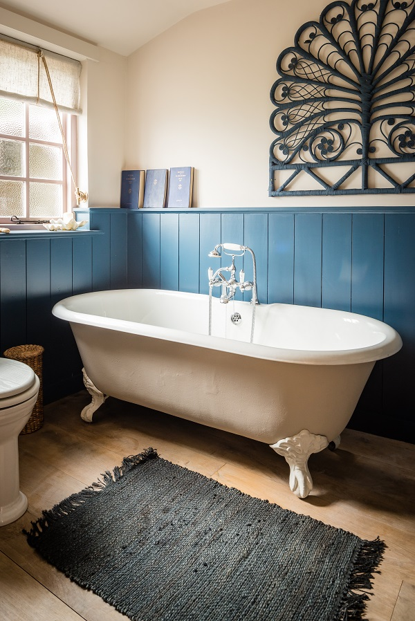 A claw foot tub in a boho-chic cottage