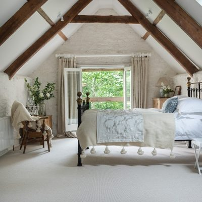 Grace and Rusticity is a bed under the eaves with the breeze wafting through an open window