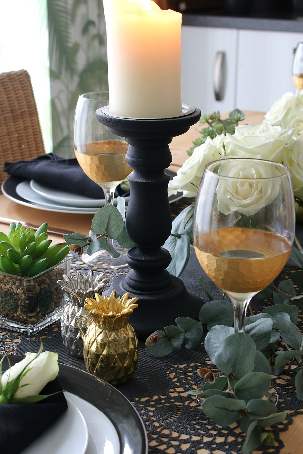 A Black And Gold Table Setting For A Special Dinner