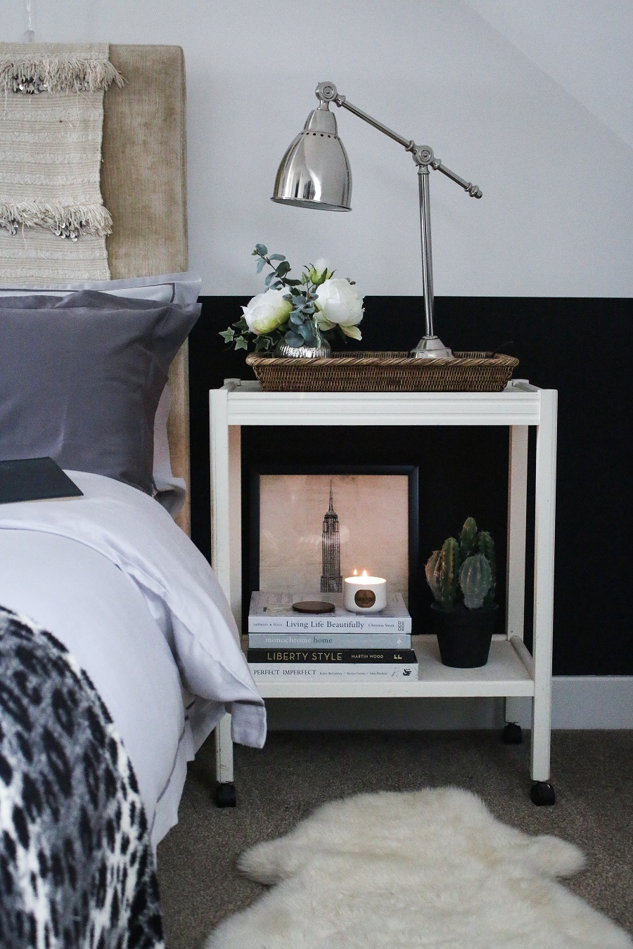 Winter bedroom with black and white half painted walls, bedside table, candle burning